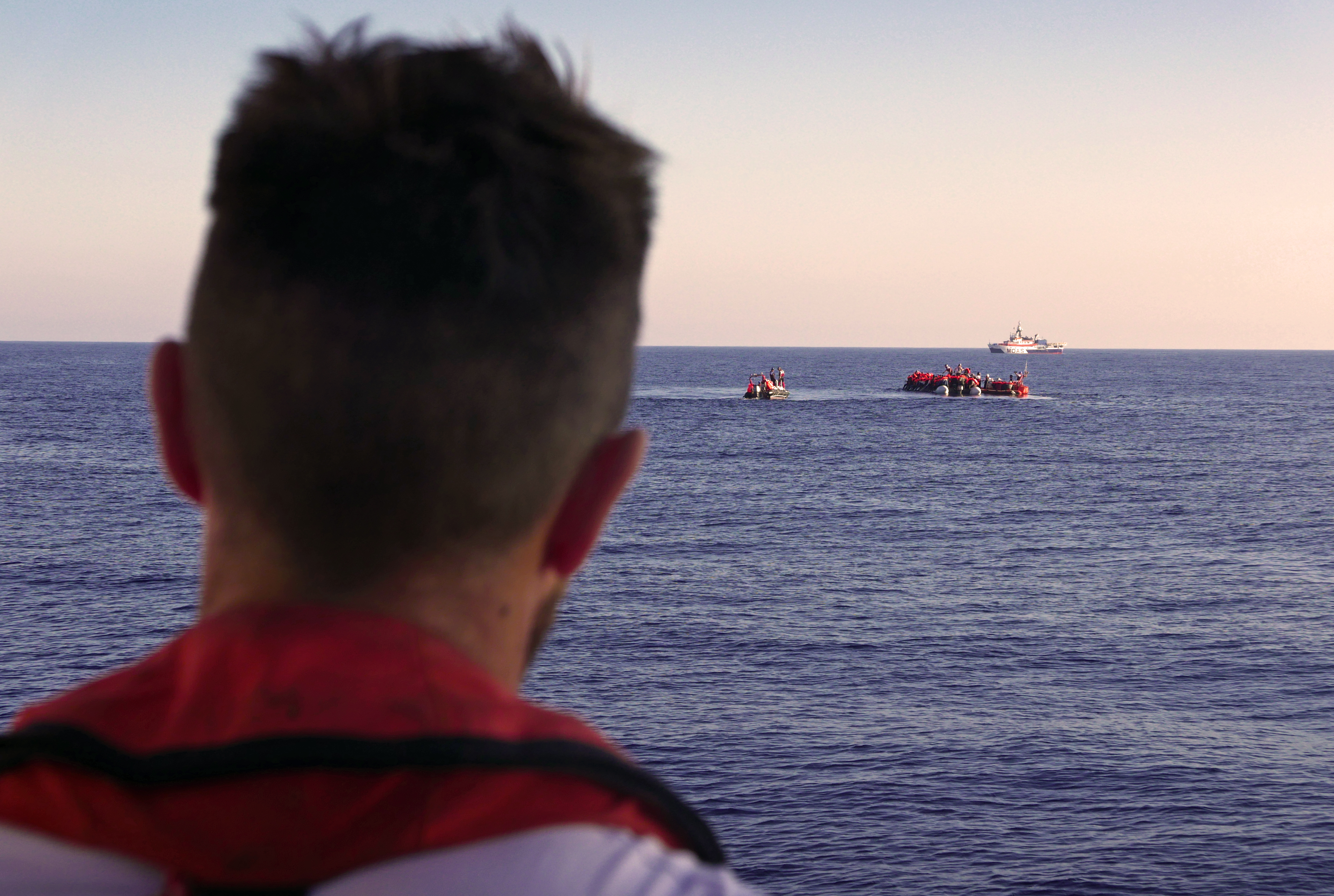 A man looks out to sea at rescue boats