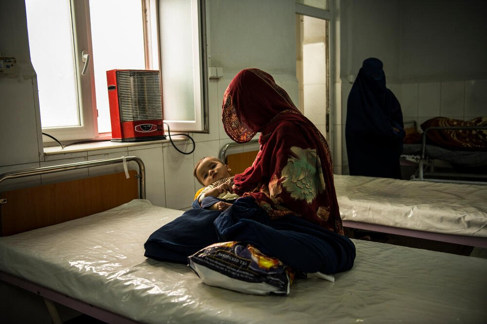 Imran, suffering from a chest infection, is held by his mother in the female observation ward at Boost hospital, October 2020. © Andrew Quilty