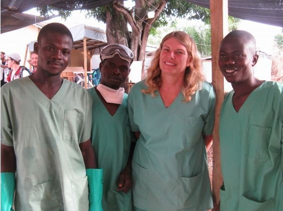Cokie poses with Water and Sanitation staff outside an Ebola treatment centre in Guinea.