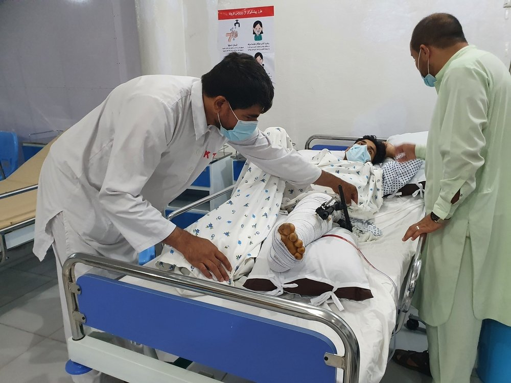 Emergency room of the MSF Kunduz Emergency Trauma Unit, a medic treats a patient who has suffered a complicated fracture of their upper and lower leg due to a bomb blast.