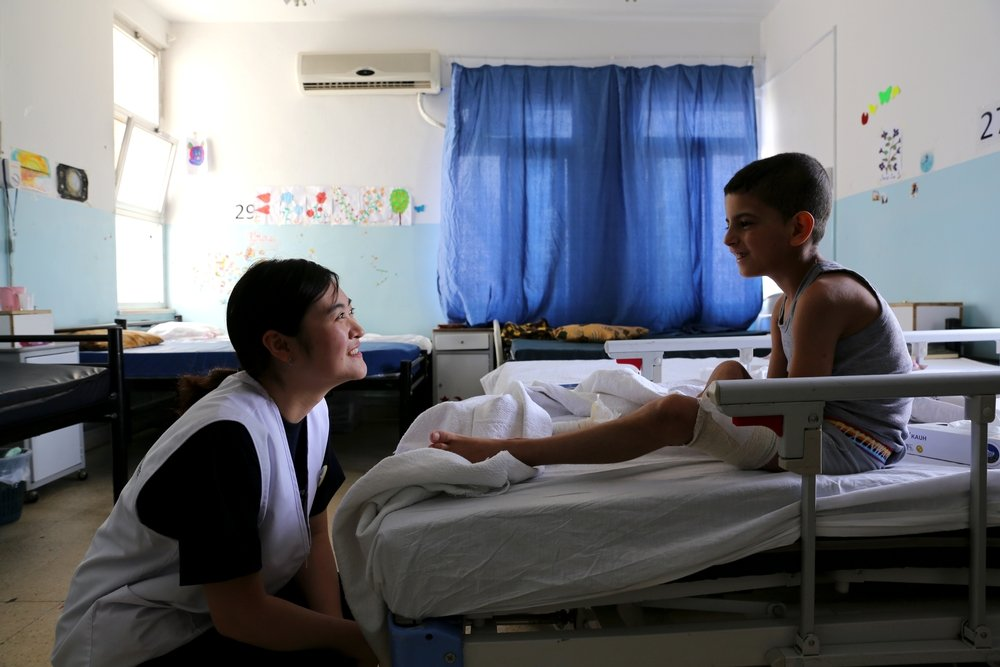 Operating theatre nurse Sunyoung Park spends time with a Syrian boy who is being treated in Ramtha hospital.