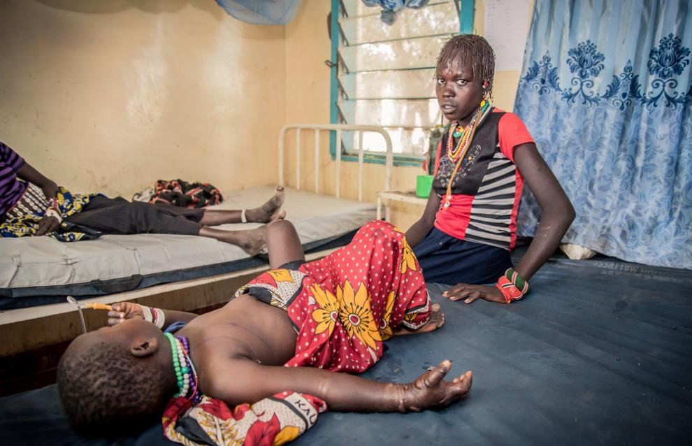 A four-year-old patient bitten by a puff adder lays next to her mother at an MSF hospital in South Sudan
