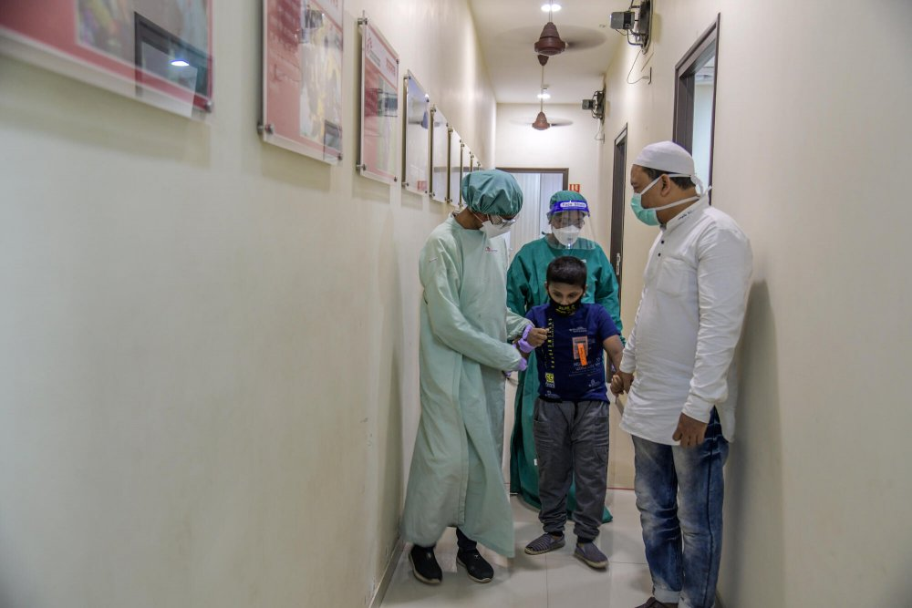 MSF medical team, helping a nine-year-old patient with extensively drug-resistant tuberculosis and extra-pulmonary tuberculosis at MSF's independent clinic in Mumbai. India, March 2021.