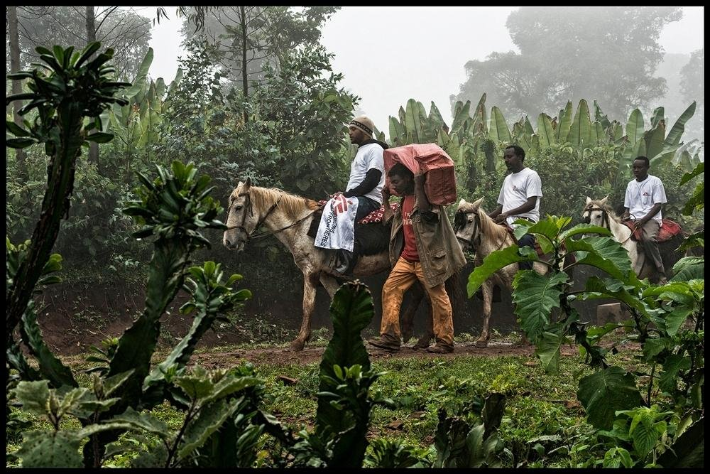 Three MSF workers on horses in a line, with a man walking beside them carrying a large bag on his shoulders.
