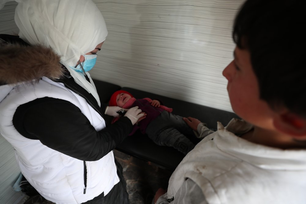 An MSF nurse examines a baby at MSF's mobile clinic, in an IDP camp in Northwest Syria