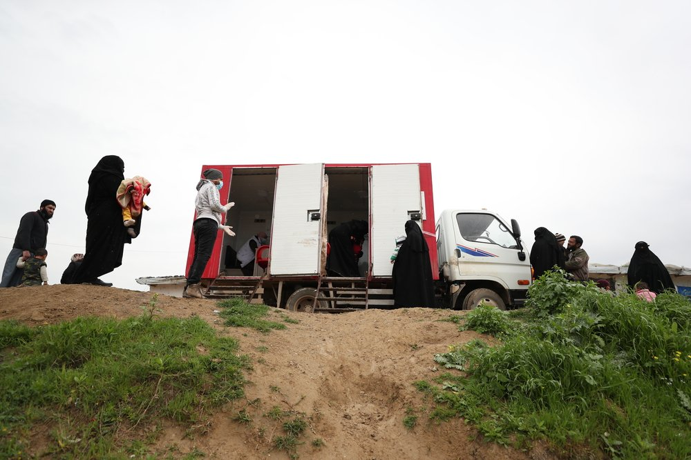 People observe social distancing measures while waiting for a consultation at MSF's mobile clinic, in an IDP camp in Northwest Syria.