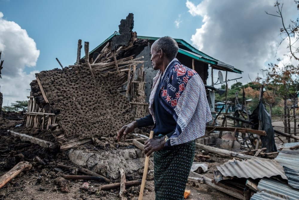 A man stands in front of his destroyed house in the village of Bisober, Ethiopia, on December 9, 2020.