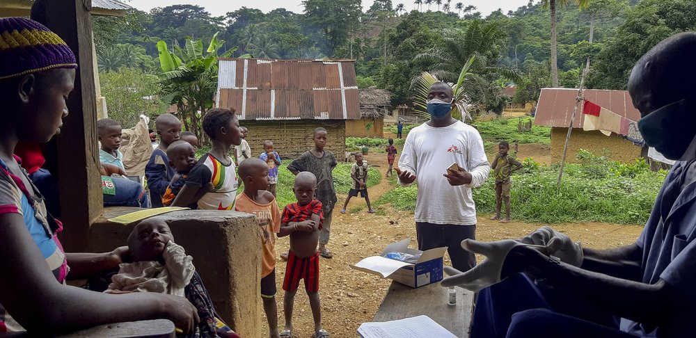 MSF health promoter Mohammed Turay delivers a health sensitisation session as people wait to be seen by a community health worker in the village of Mbaama, Kenema District