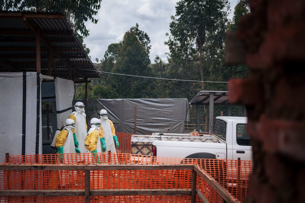 Health workers escorting an Ebola victim after the placement of the body bag in the coffin.
