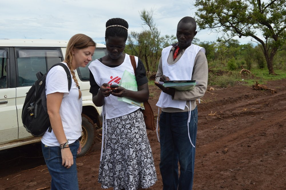 MSF staff members pause on the road to look at the location of a sample household in Palorinya refugee settlement, northern Uganda.