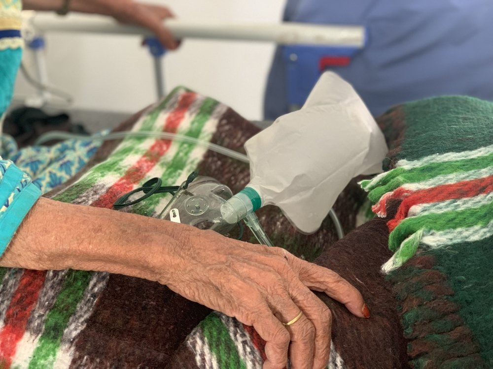 An elderly female patient removes her oxygen mask to talk to medical staff in the mSF-supported Sheikh Zayed COVID-19 treatment center in Sana'a.