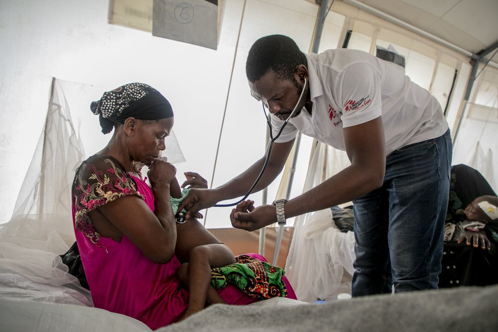 An MSF doctor listens to the heartbeat of a child hospitalised at a measles treatment centre in Mayi-Munene, DRC.
