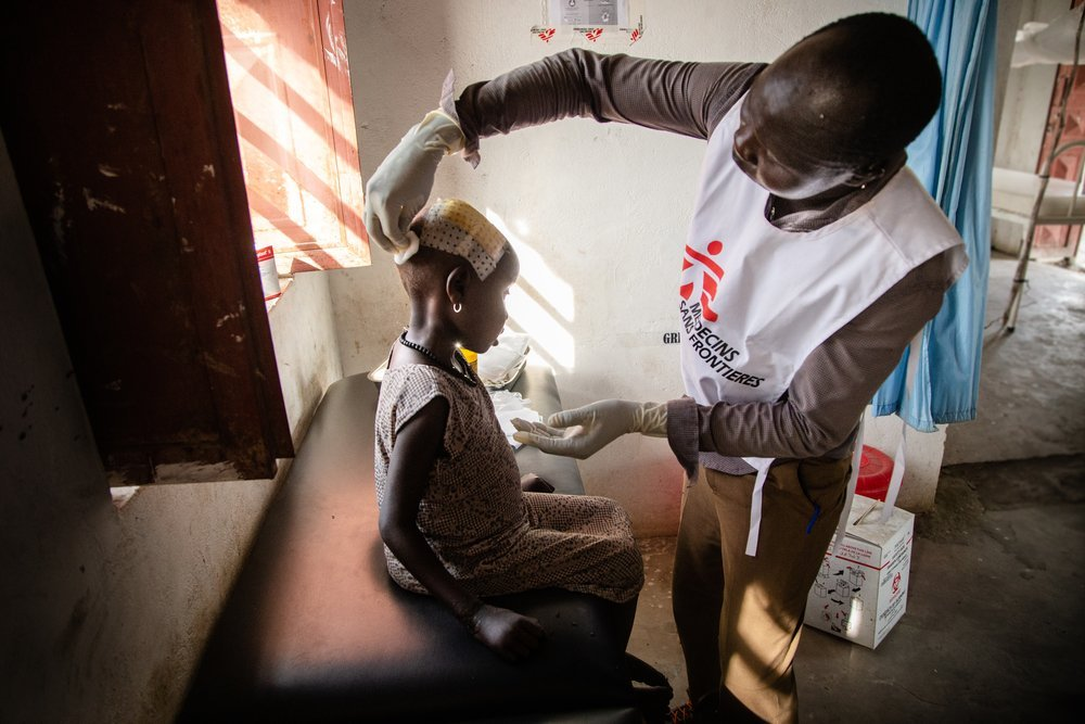 An MSF staff member examines the head injury of a young girl at a hospital in Ulang.  Northeast South Sudan, April 2019.