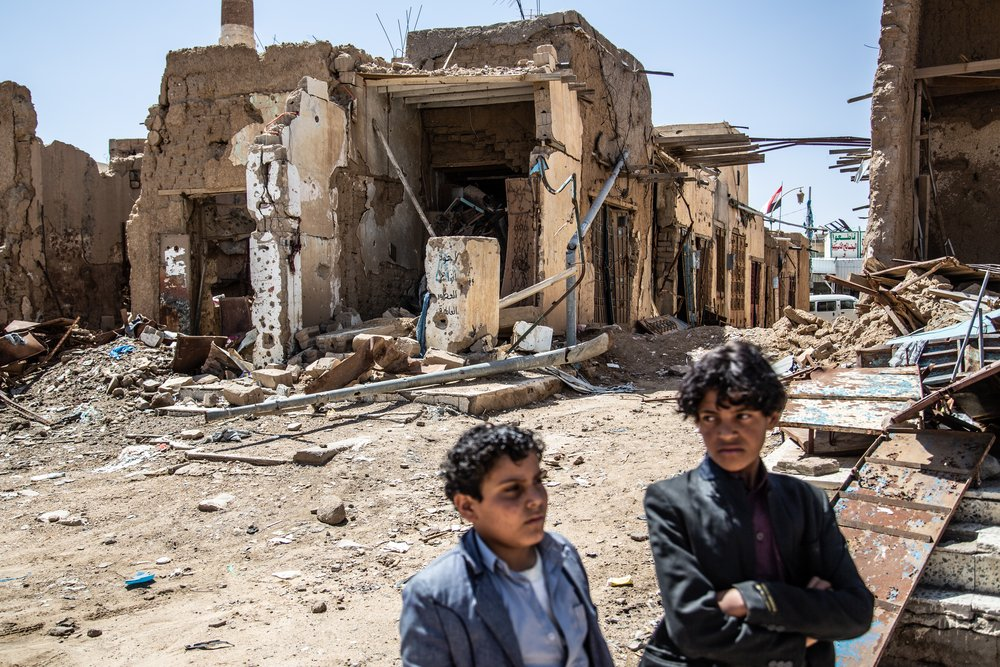 Two boys stand outside a park and several shops that were bombed in an airstrike near the old city of Saada, Yemen.