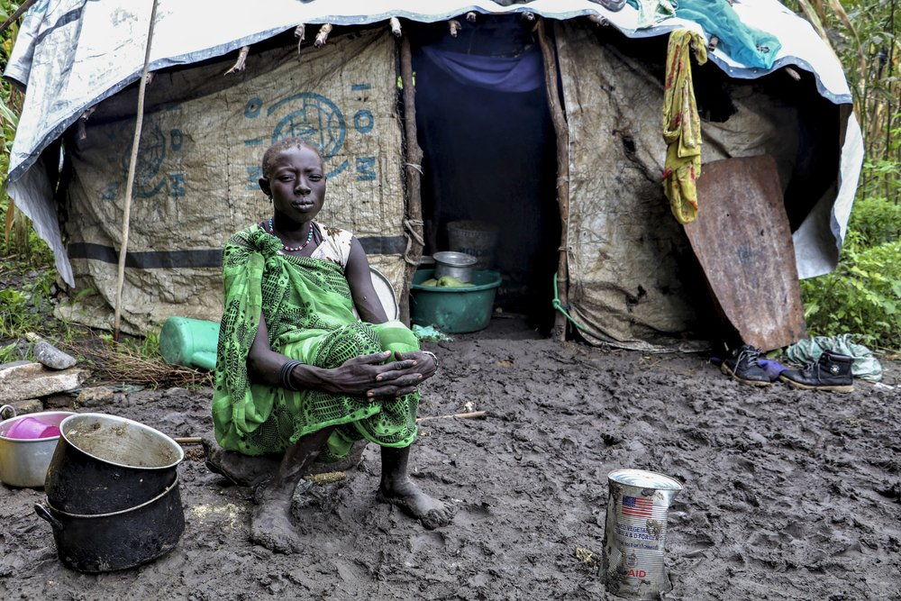 A young woman sitting in front of her shelter in Lukurunyang after heavy rainfall destroyed her crops.
