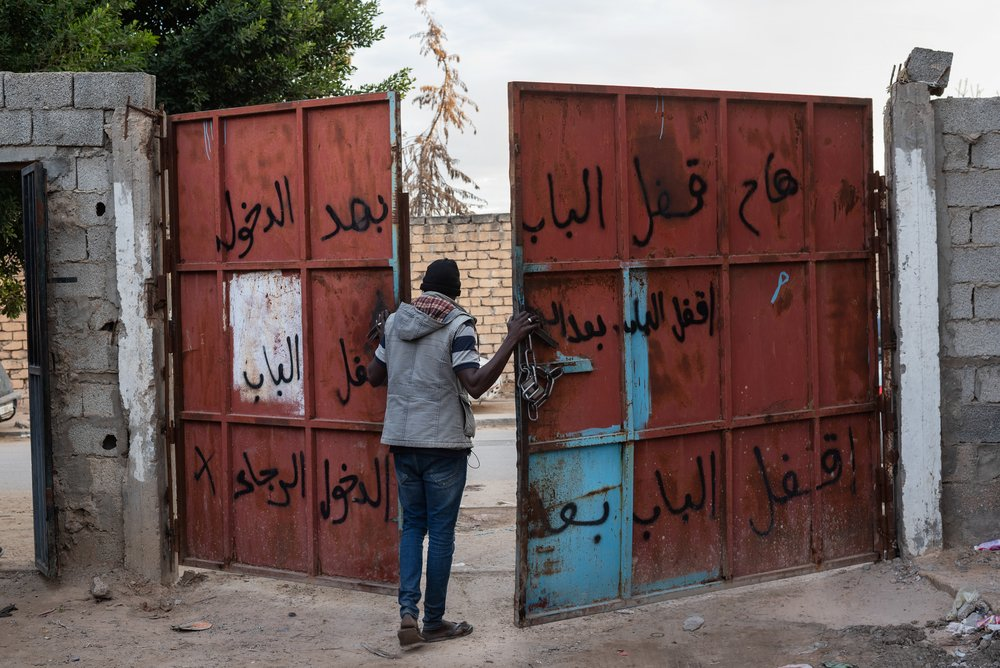 A refugee from Darfur, Sudan opens the gate entrance of the area where a group of refugees live, in Gorgi district.