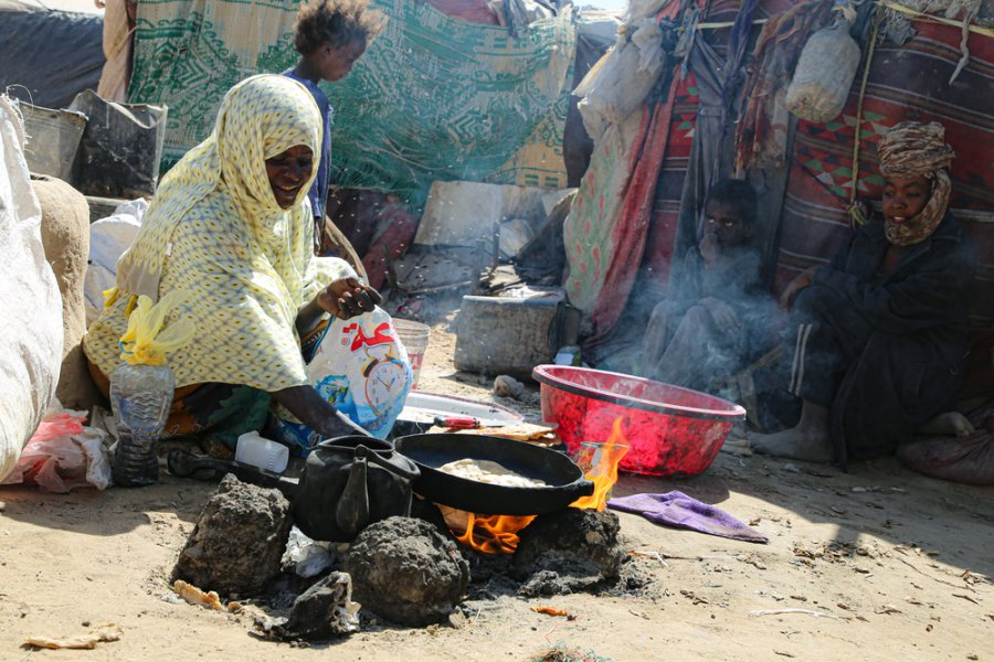 Life in Hareeb Junction camp in Marib. A woman making her lunch of bread and tea. To fuel the fire she uses trash.