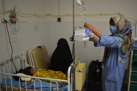 MSF nurse Fatima, pictured giving IV fluid to a malnourished child in the ICU room of the ITFC, Herat regional hospital.