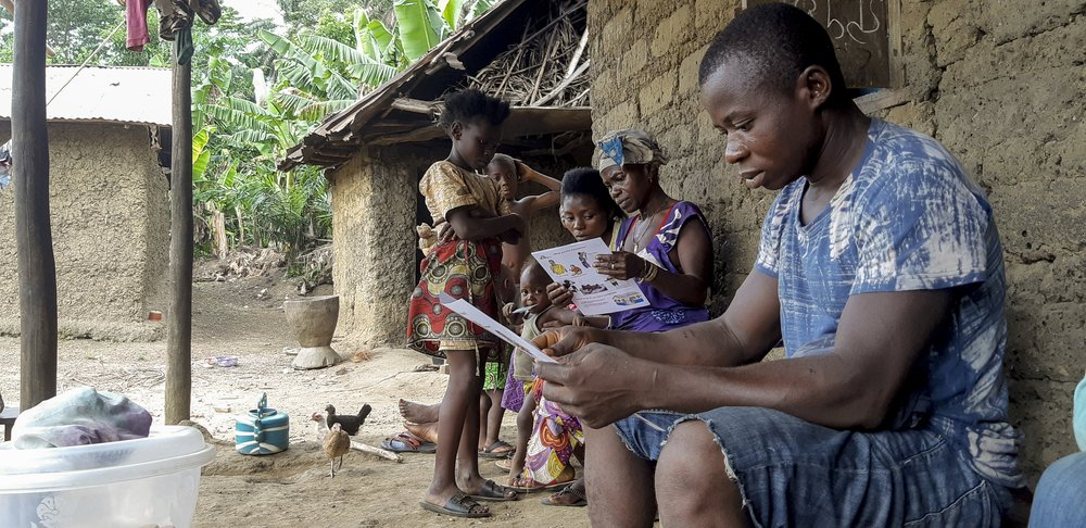 Residents of Bomboma village, Kenema District, view leaflets explaining how to prevent transmission of COVID-19 after a sensitisation session by an MSF health promoter.