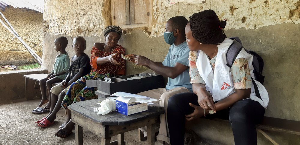 A community health worker dispenses malaria medication in the village of Gbapi, Kenema District