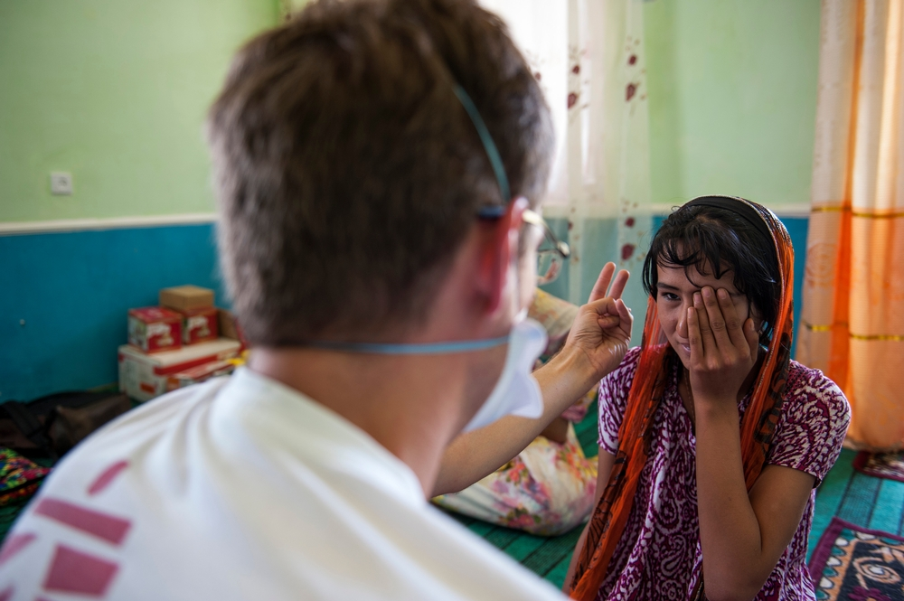 A young women covers one eye while an MSF health worker conducts an eye test.