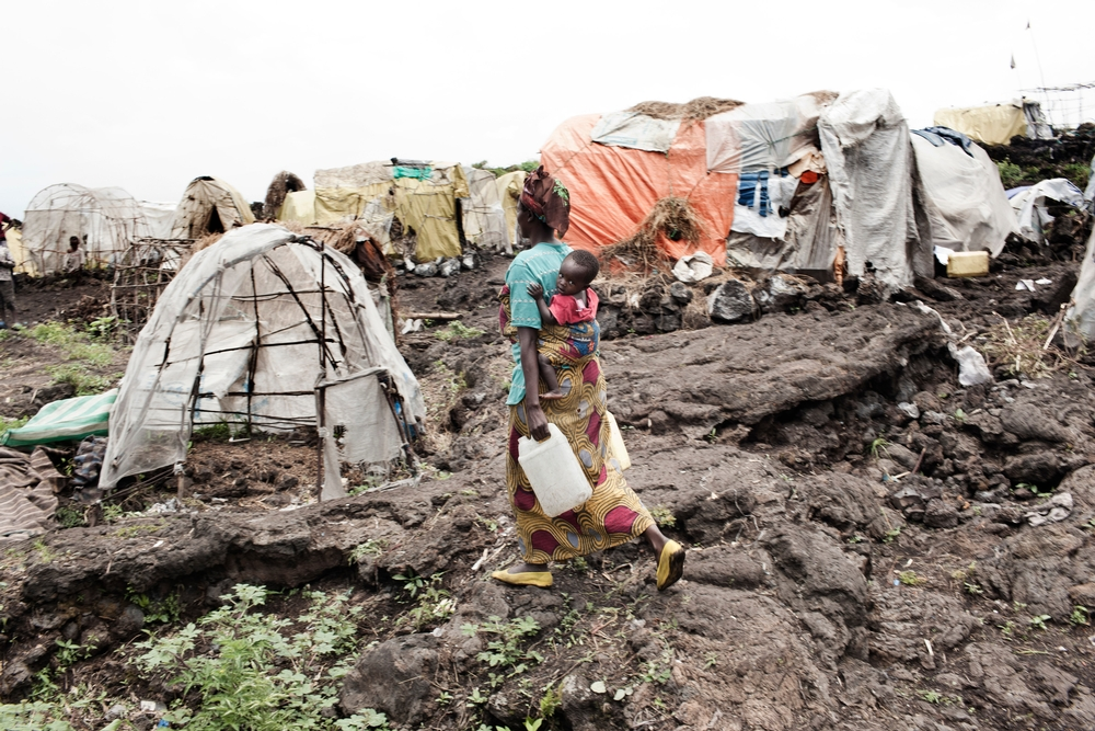 A woman carrying a baby on her back and two water containers walks across rocky ground towards makeshift tents.
