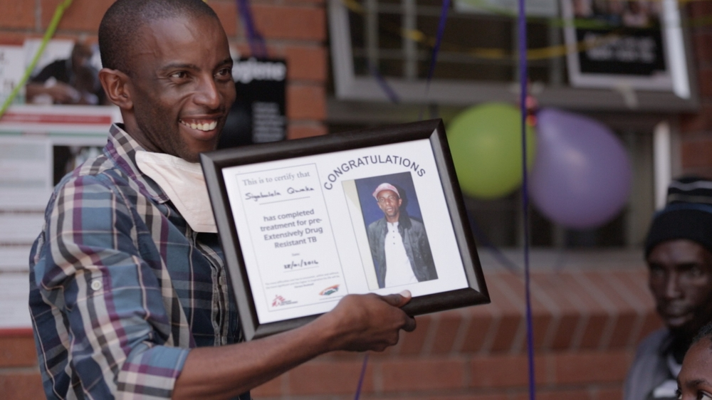A smiling man holds a framed certificate for completing treatment for pre-extensively drug-resistant TB