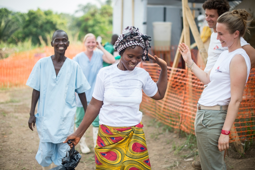 Two health workers in MSF shirts and two others in scrubs smile and wave at a woman.