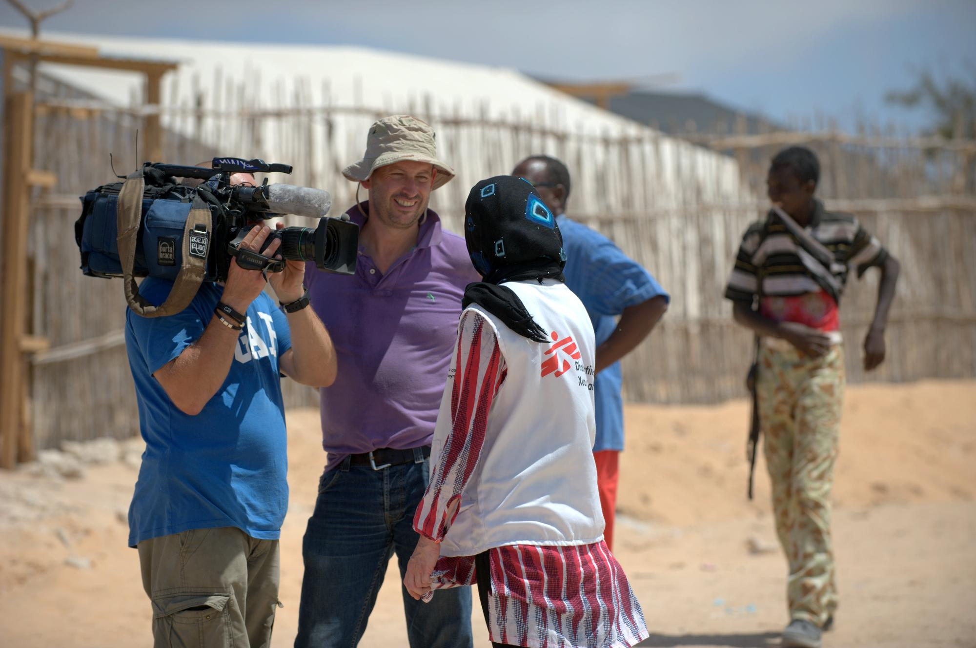 Two men, one with a camera, talk to a woman wearing an MSF shirt and a head scarf. Two men walk in the background, one of them carries a gun.