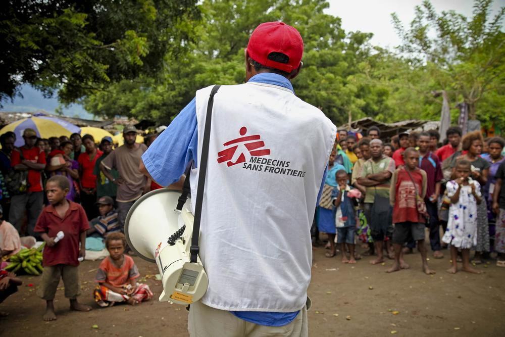 An MSF worker with a bullhorn stands in front of a crowd of locals.