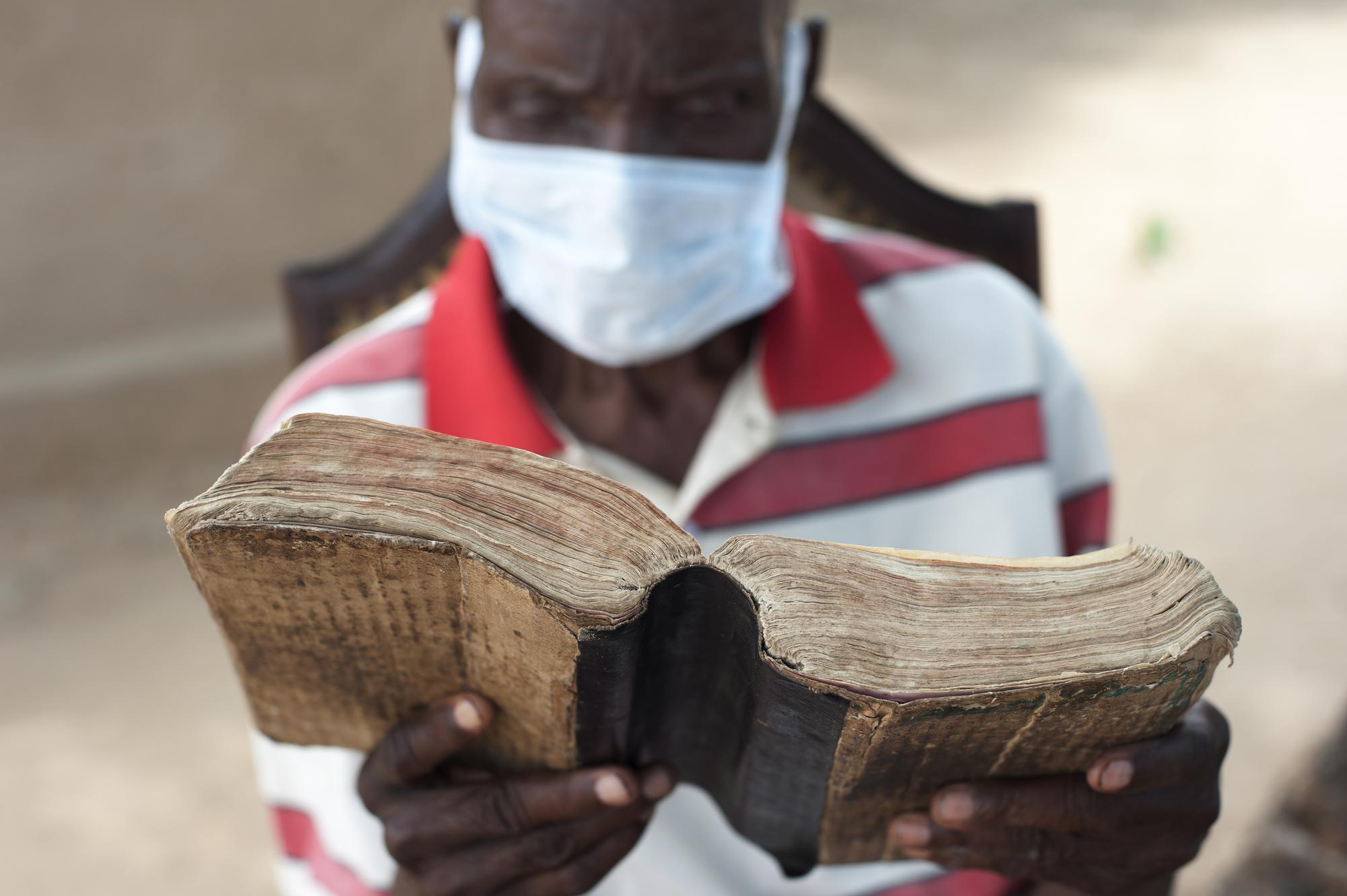 A man wearing a surgical mask reads a well-worn book.