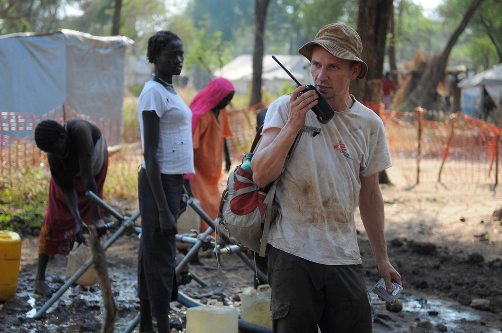 A man in an MSF shirt uses a 2 way radio, while in the background women fill containers with water