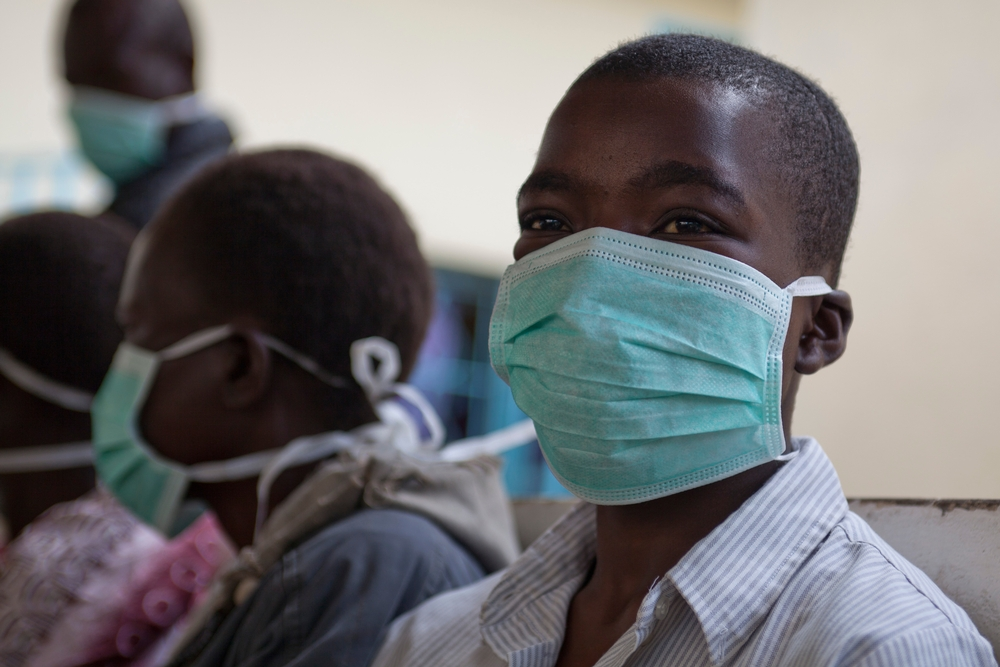 A boy wearing a surgical mask smiles.