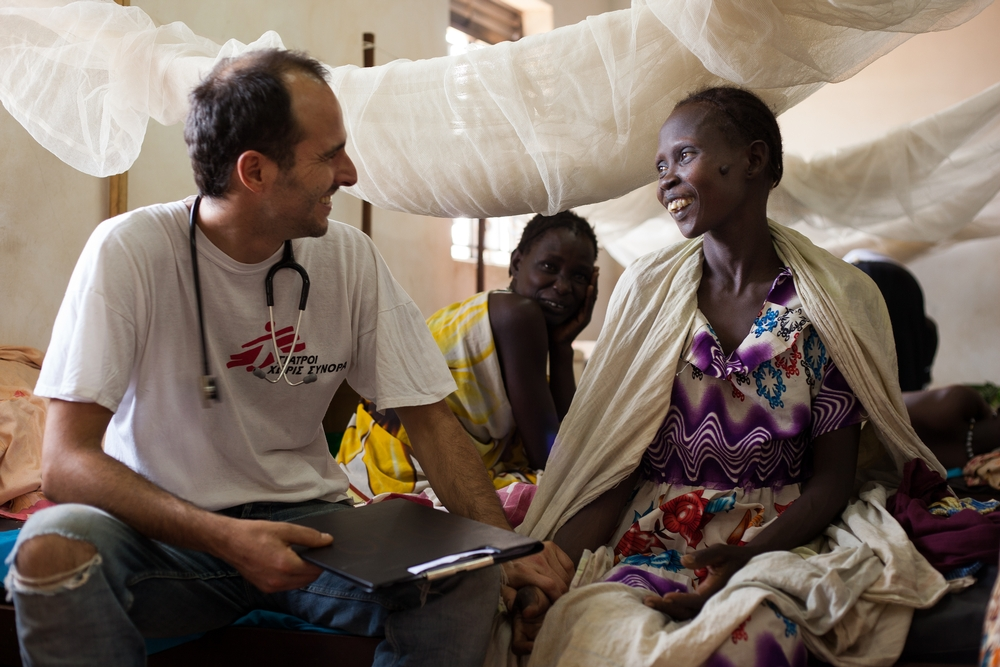 A woman and an MSF doctor sitting and smiling at each other, while another woman smiles in the background