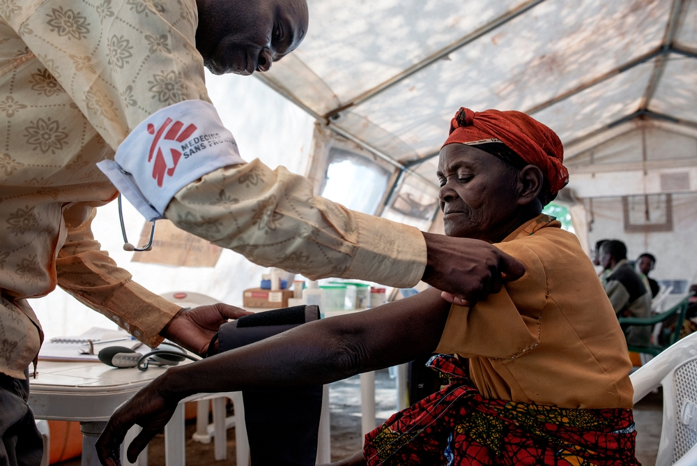 MSF health worker checks the blood pressure of an elderly woman.