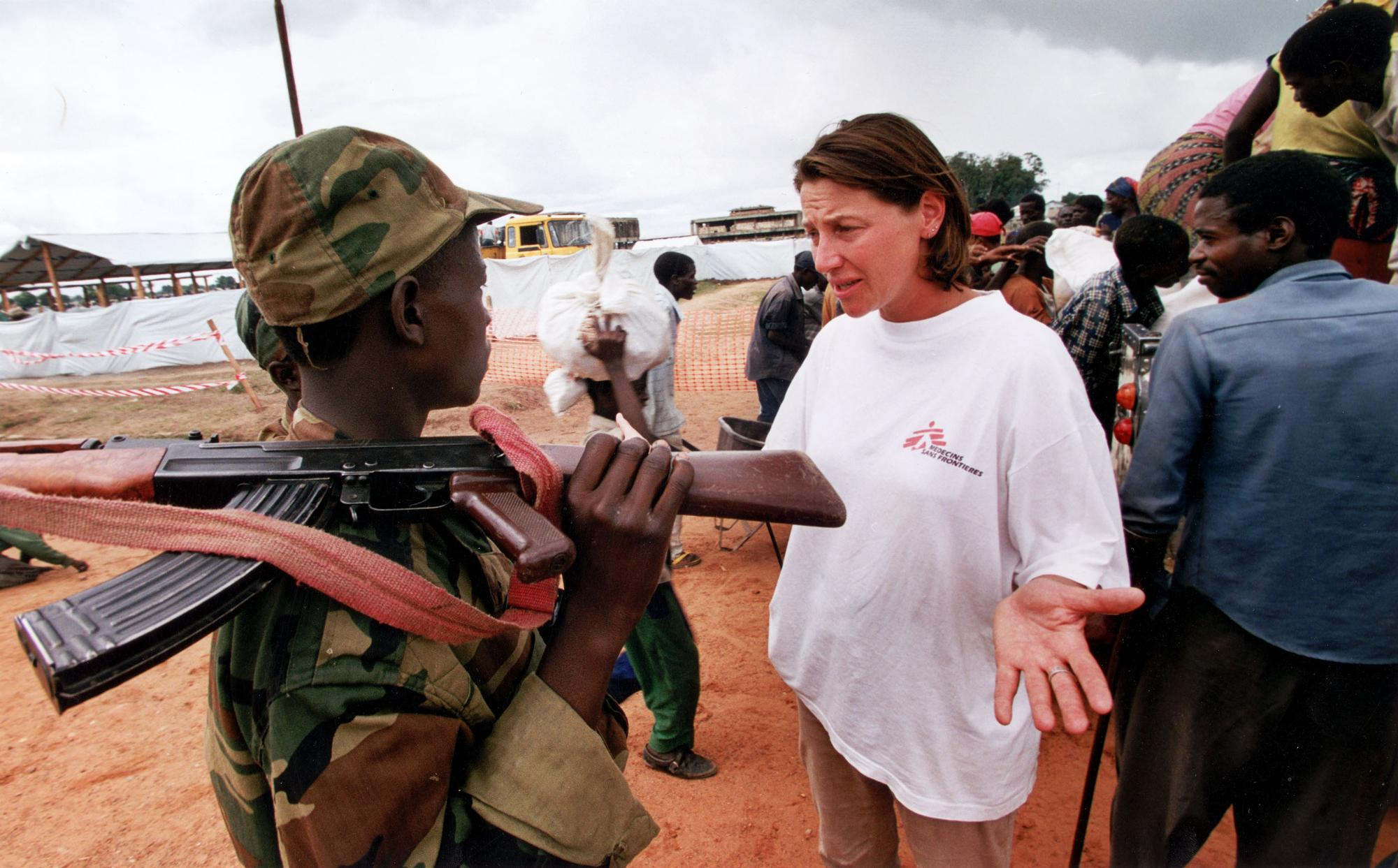 An MSF worker talks to an armed soldier in front of a line of people.