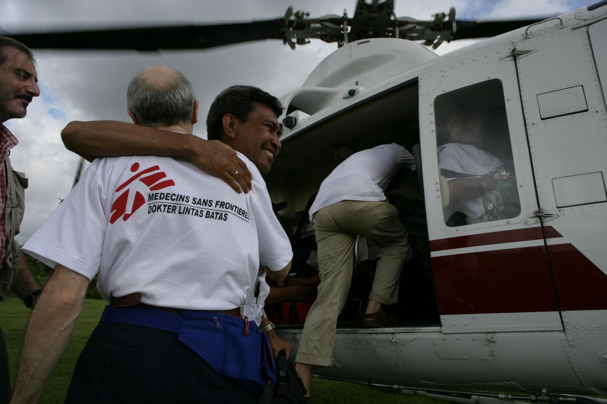 A group of people standing close to a helicopter. One man hugs an MSF worker.