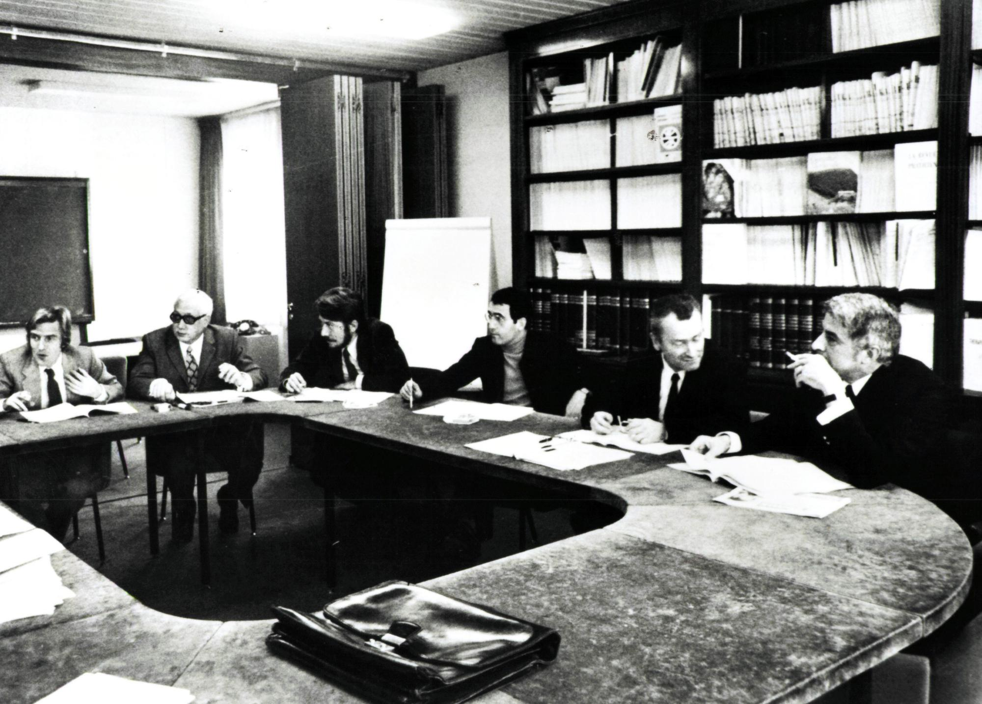 An old black and white photo of a group of men sitting around a large office table with bookshelves in the background.