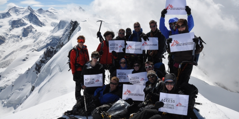 A group of smiling climbers stand on a snowy mountain holding MSF signs.