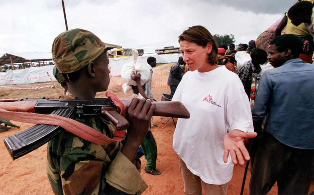 A woman in an MSF shirt speaks to two armed soldiers next to a queue of people