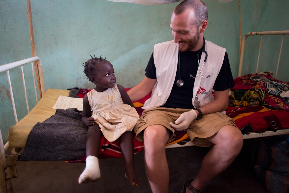 An MSF health worker sitting next to a child with a foot cast and smiling at her.