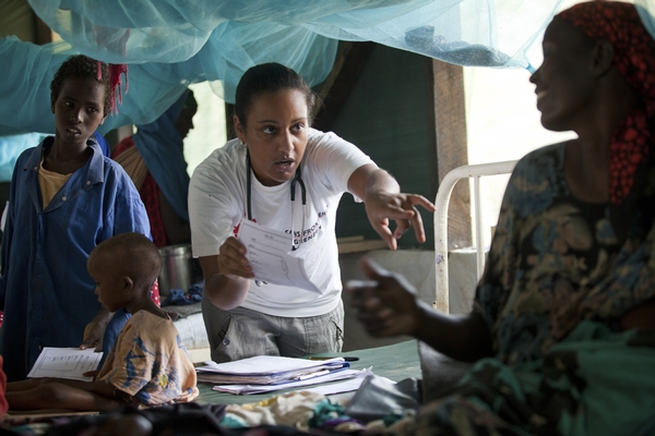 An MSF worker in a health centre speaks to a patient sitting on a bed. Children in the background look on.