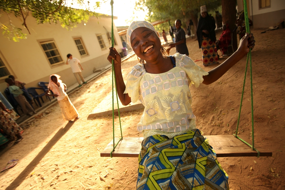 A patient in Nigeria siting on a swing and smiling