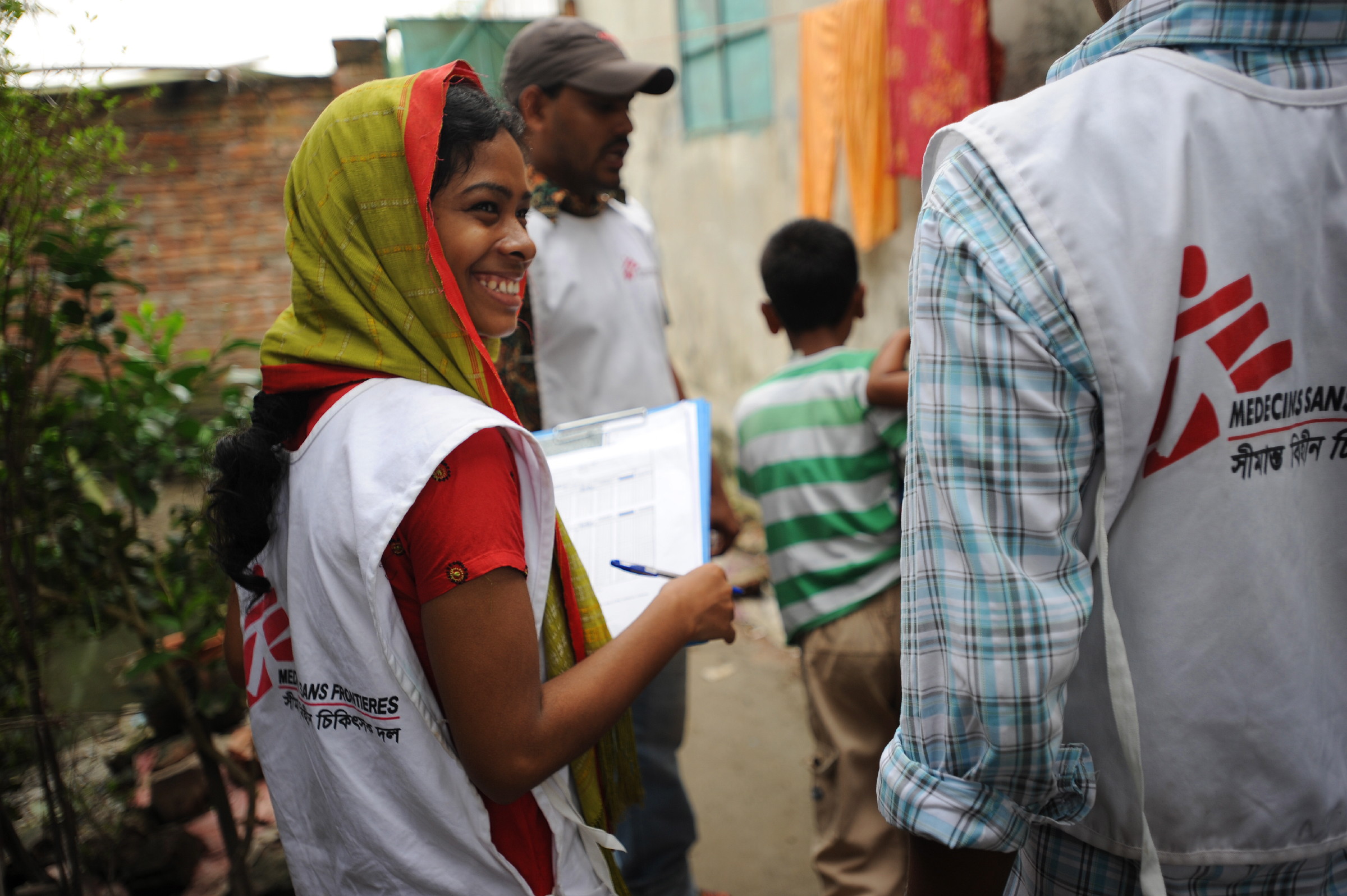 A woman wearing an MSF shirt and a head scarf holds a clip board and smiles at another MSF worker partially out of frame.