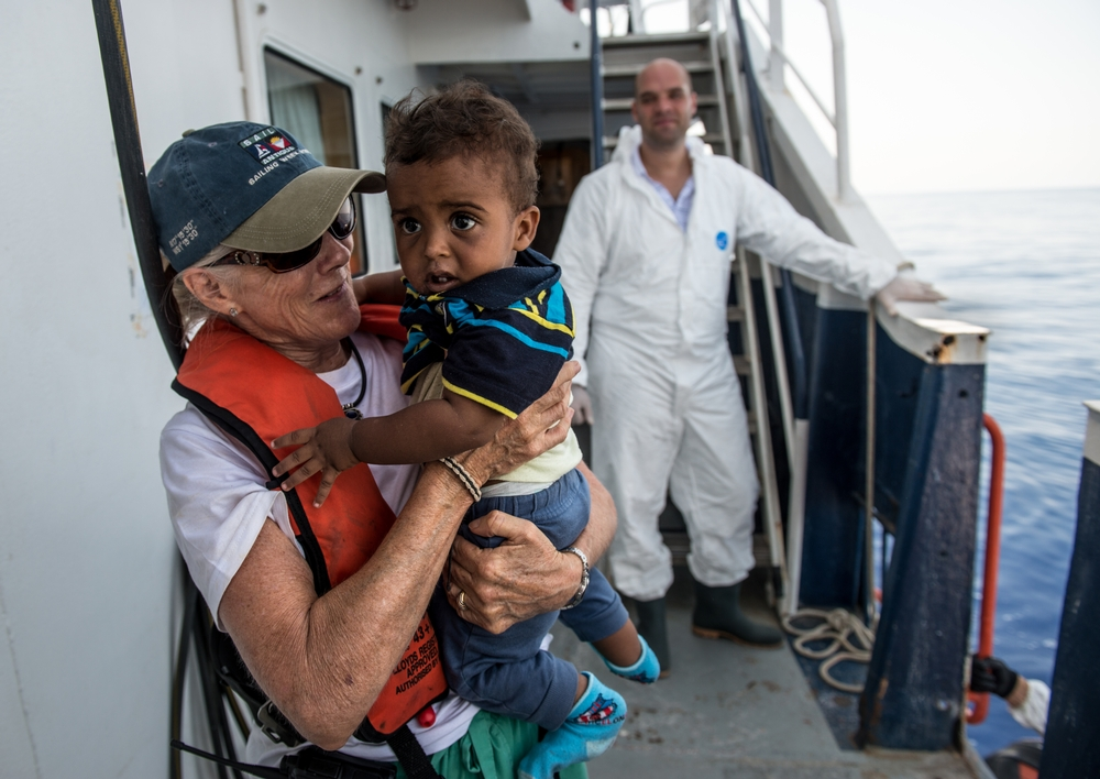 An MSF worker on a ship, wearing a lifejacket smiles at a toddler in her arms, as a man wearing coveralls smiles in the background.