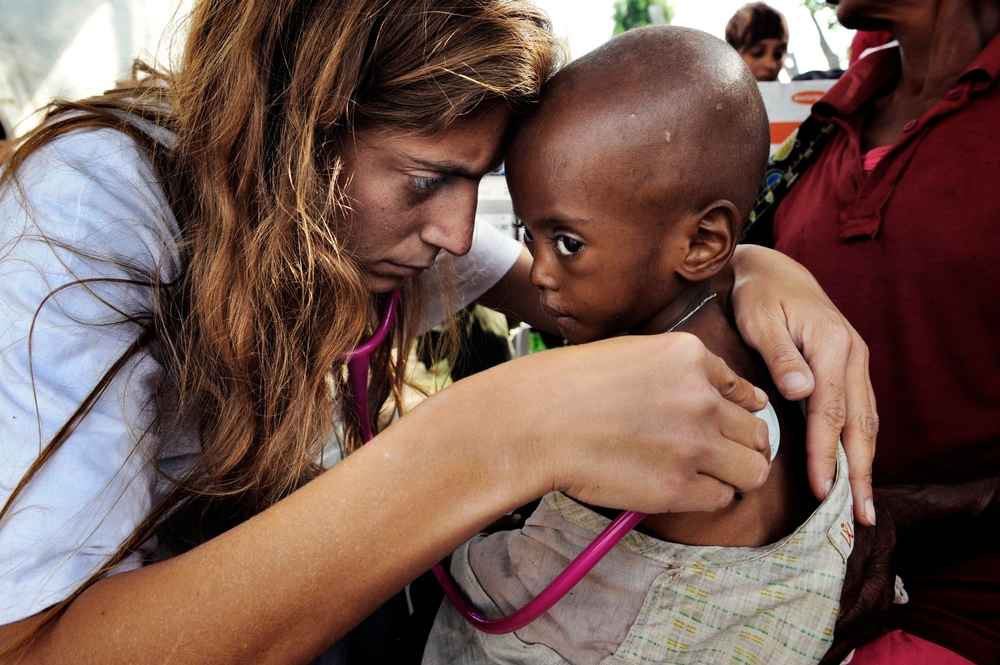 Woman with stethoscope tends to a small, malnourished child