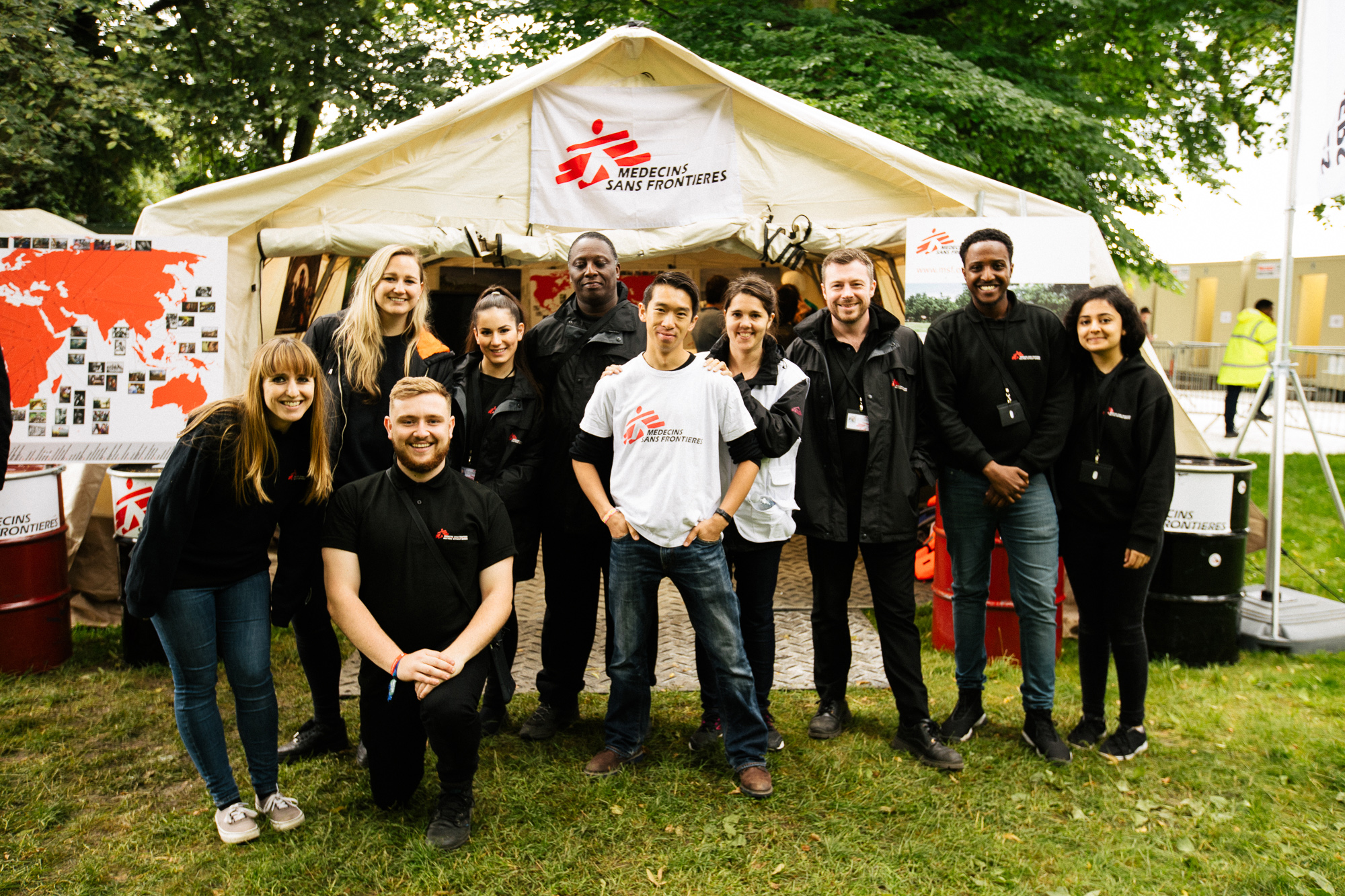 A group of fundraisers wearing MSF clothing pose for a photo outside a large MSF tent